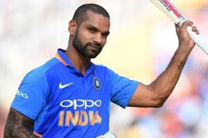 India cricketer Shikhar Dhawan raises his bat to acknowledge the crowd as he walks back after his dismissal during the fourth one-day international (ODI) cricket match between India and Australia at the Punjab Cricket Association Stadium in Mohali on March 10, 2019.