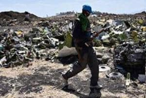 An Oromo man hired to assist forensic investigators walks by a pile of twisted airplane debris at the crash site of an Ethiopian airways operated Boeing 737 MAX aircraft on March 16, 2019 at Hama Quntushele village near Bishoftu in Oromia region. - A French investigation into the March 10 Nairobi-bound Ethiopian Airlines Boeing 737 MAX crash that killed 157 passengers and crew opened on March 15 as US aerospace giant Boeing stopped delivering the top-selling aircraft. (Photo by TONY KARUMBA / AFP)