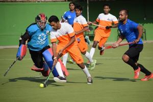 Prabhakar Aspat Academy (orange) in action against Excellency Academy in the semi-finals of the first Friendship Cup invitational hockey tournament at Major Dhyan Chand hockey stadium, Pimpri on Tuesday.