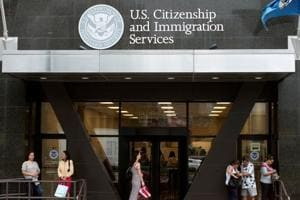 People stand on the steps of the US Citizenship and Immigration Services offices in New York.