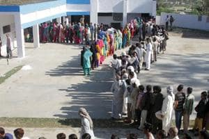 Voters stand in a queue at a polling station in Jammu.