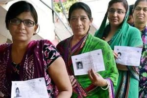 Women wait to cast their vote at a booth in Ahmedabad's Daskroi constituency.