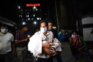 Patients being evacuated after  a fire broke out at  a basement  near the Trauma Centre of the All India Institute of Medical Sciences in New Delhi Sunday evening.