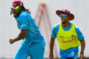 Chris Gayle (L) and Nicholas Pooran (R) of West Indies take part in a training session.