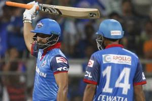 Delhi Capitals Rishabh Pant, left, raises his bat after scoring 50 runs.