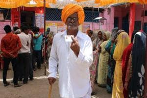 Madhya Pradesh, May 19 (ANI): Voter shows his ink-marked finger and voter ID card at a polling station after casting their vote at Rajod village in Dhar district in Madhya Pradesh on Sunday.