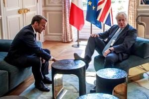Brexit on plate and foot on table in UK PM Boris Johnson's France visit