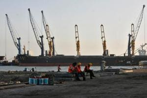 Worker rest in front of a cargo ship at a port in Gujarat.