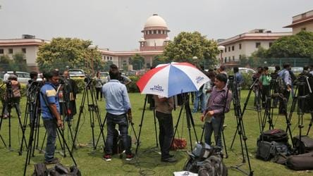 Television journalists are seen outside the premises of the Supreme Court in New Delhi, India August 22, 2017. REUTERS/Adnan Abidi