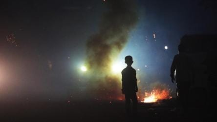 A child stands in front of smoke emitted from burning firecrackers in east Delhi on Diwali night.