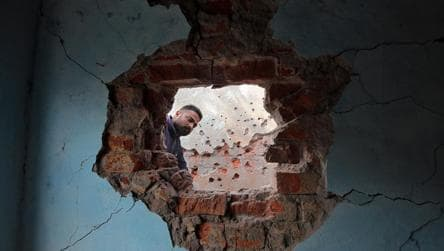 A man looks at the wall of his house that was damaged by firing from the Pakistan side of the border at Kanachak in Akhnoor Sector on the outskirts of Jammu.