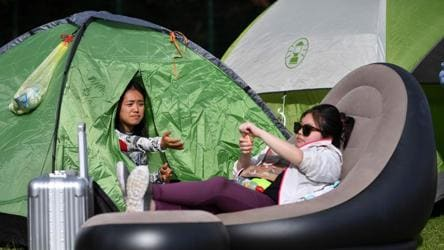 A couple of girls sit in their tents while they camp for a spot further up in the queue to buy tickets on the first day of the 2019 Wimbledon Championships tennis tournament. Wimbledon is one of few remaining major sporting events in the United Kingdom that still sells tickets on the day of play.