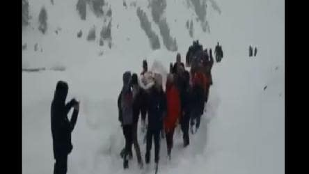 Sick policeman carried by locals and fellow policemen in knee-deep snow. Watch