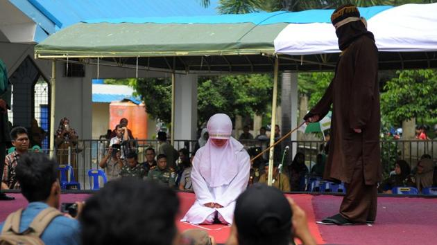 An Acehnese religious officer canes a woman 100 times for having sex outside marriage, which is against sharia law, in Banda Aceh on Monday.(AFP)