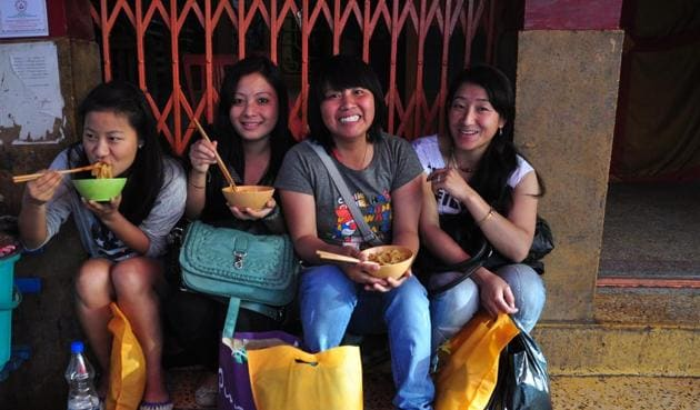 Girls enjoys the street food of Tibet at Majnu Ka Tila market.(Sarthak Nagpal/HT Photo)