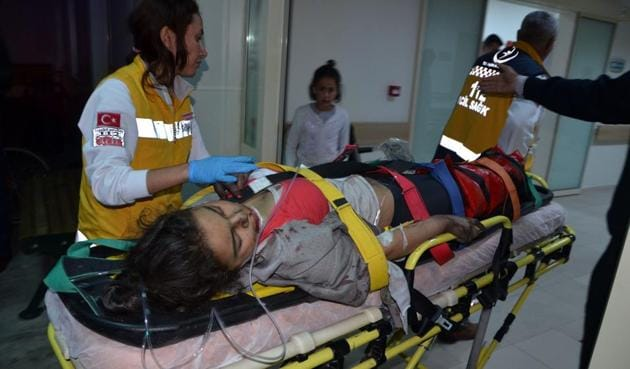 An injured girl taken to hospital following a fire at a school dormitory in Adana, southern Turkey.(AP Photo)