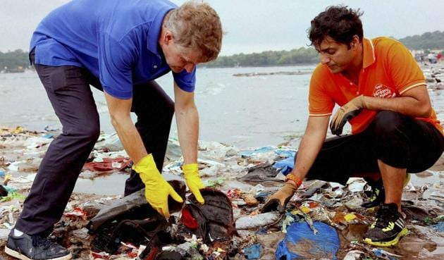 Mumbai-based lawyer Afroz Shah (right) and Erik Solheim, head of United Nations Environment, clean the Versova beach in Mumbai.(PTI)