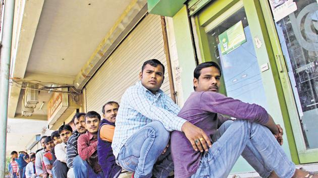 People wait for cash outside the Oriental Bank of Commerce ATM in Gurgaon(HT File Photo)