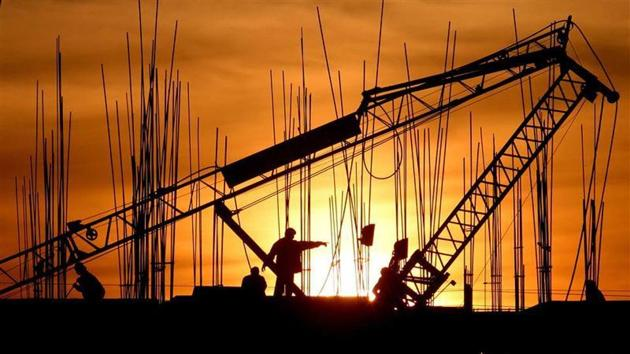 Construction workers work at a site as the sun sets in Chandigarh December 16, 2006. REUTERS/Ajay Verma/Files(REUTERS)