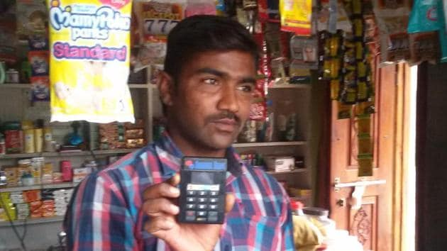 A provisions store owner in Ibrahimpur displays a Point of Sale machine for selling goods using smart cards.(HT photo)
