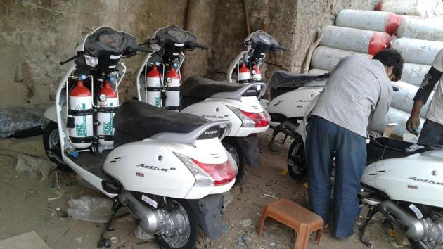 A mechanic fits scooters with CNG cylinders.(HT)