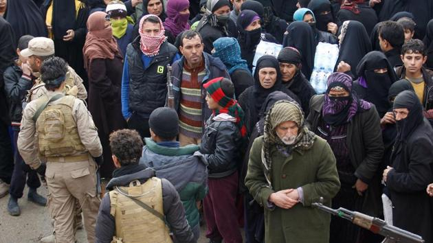 Displaced Iraqis from Mosul, who are fleeing Islamic State militants, gather to receive aid.(Reuters photo)
