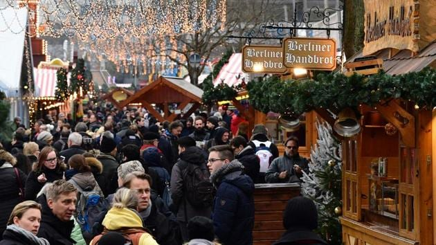 People walk between booths at the Christmas market near the Kaiser-Wilhelm-Gedaechtniskirche (Kaiser Wilhelm Memorial Church) in Berlin on December 22, 2016. The Berlin Christmas market that was struck by a deadly truck rampage on December 19, 2016 reopened, as the grieving city sought a return to normal life and police hunted for the prime suspect in the attack.(AFP)