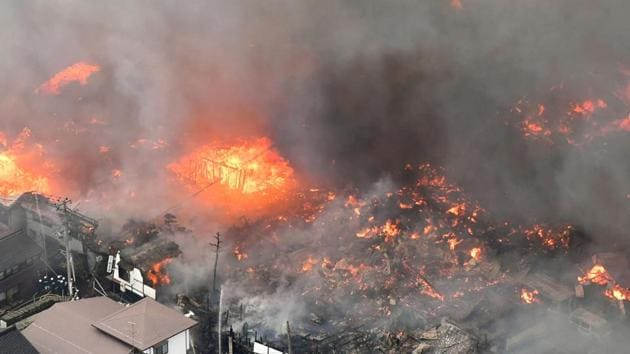 A fire engulfs houses and stores near JR Itoigawa Station in Itoigawa, Japan on Thursday.(Reuters photo)
