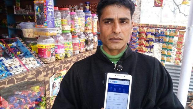 Shabir Ahmed Lone, a grocer in Lanura village in Jammu and Kashmir, has Paytm app on his smartphone but says that villagers are still using cash.(Waseem Andrabi / Hindustan Times)