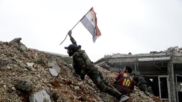 A Syrian army soldier places the national flag during a battle with rebel fighters at the Ramouseh front line, east of Aleppo.(AP Photo)