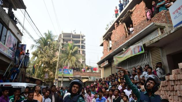 Bangladesh police officials stand alert as bystanders gather at the scene of an operation to storm an alleged militant hideout in Dhaka on Saturday as a team from the counterterrorism unit of Dhaka Metropolitan Police cordoned off a three-storey building in the capital.(AFP)