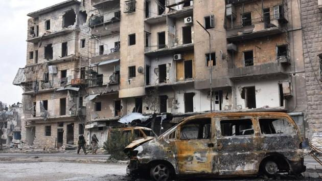 Syrians government forces walk past destroyed buildings in the former rebel-held Ansari district in the northern Syrian city of Aleppo.(AFP Photo)