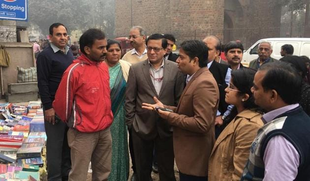 North Delhi Municipal Corporation officials (right) explains the benefits of using card swipe machines or going cashless to a vendor who sells used books at the weekly market in Daryaganj on Sunday.(Handout)