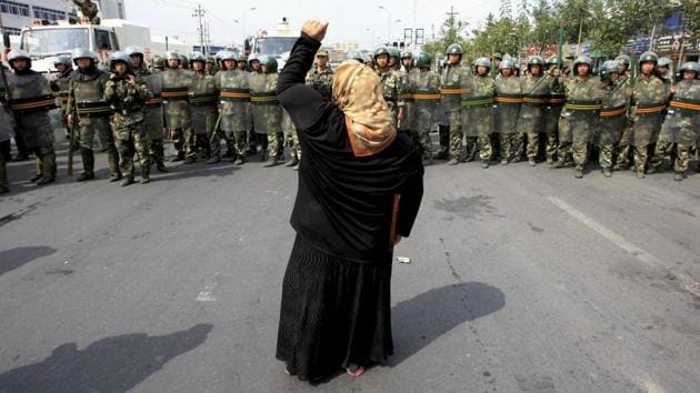 A local woman confronts security forces in Urumqi in China's Xinjiang Autonomous Region. In the region, home to Muslim Uyghurs, restrictions have been put in place on growing a beard and wearing a veil.(Reuters file)