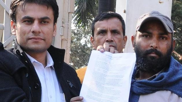 Deepak Kumar(right) being given appointment letter after he climbed down from a mobile tower near the Punjab Bhawan in Sector 3, Chandigarh, on Saturday.(Anil Dayal/HT Photo)