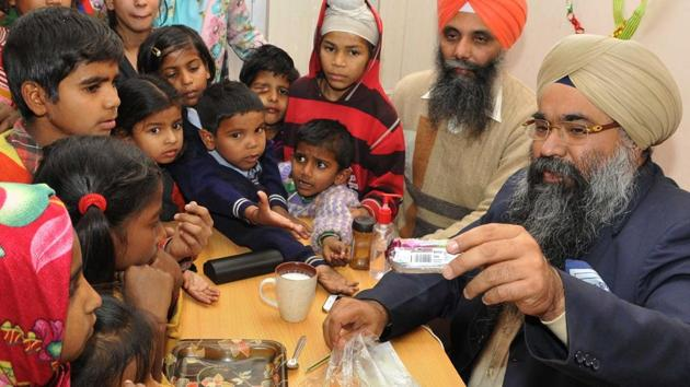 Inderpreet Singh Chadha, who funds for medicines worth Rs 10 lakh for around 500 patients every month, distributing sweets and biscuits among poor children.(Keshav Singh/HT Photo)