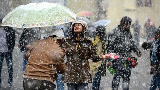 A woman enjoys this year's first snowfall in Shimla on Sunday.(Deepak Sansta /HT Photo)