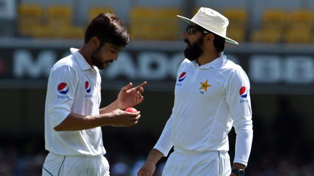 Pakistan's captain Misbah ul-Haq (R) gives instructions to Mohammad Amir (L) during the 3rd day of the 1st Test against Australia.(AFP)