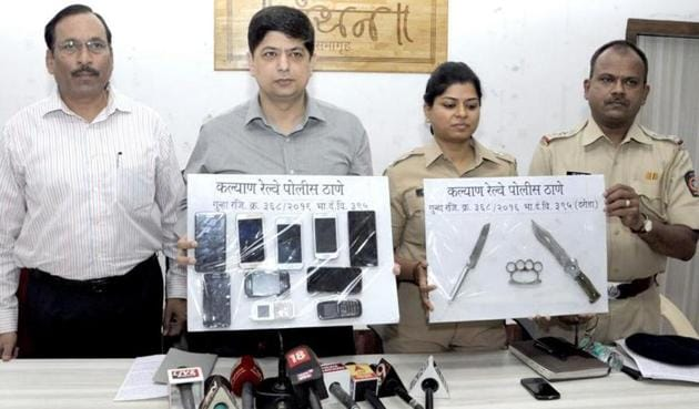 The GRP personnel with the 10 robbed mobile phones and arms used in the crime that they recovered from the accused.(HT Photo)