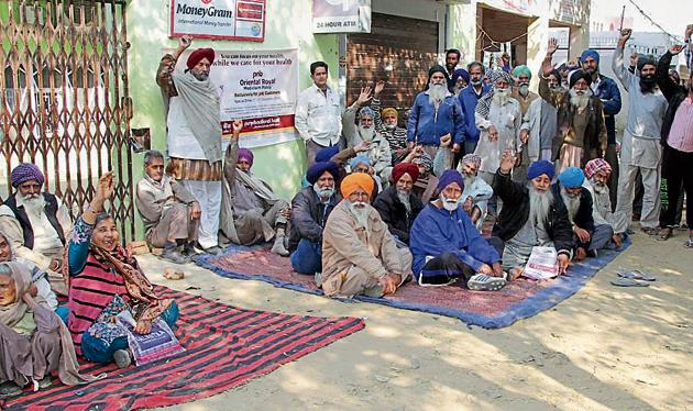 Customers protesting outside Punjab National Bank branch at Dhandra village on Monday.(JS Grewal/HT)