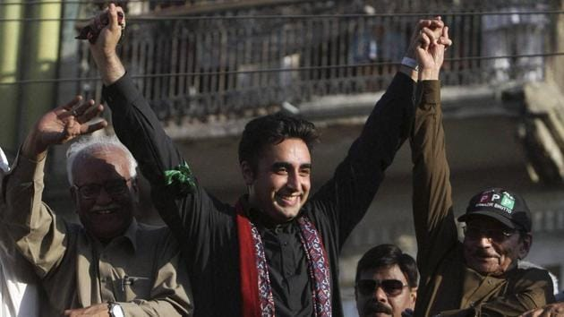 Bilawal Bhutto Zardari, center, chairman of the Pakistan People's Party, raises hands with party aides during a rally in Karachi, Pakistan.(AP Photo)