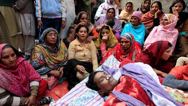 Family members mourn near the body of a man who died after consuming locally made toxic liquor, in Toba Tek Singh, Pakistan.(REUTERS)