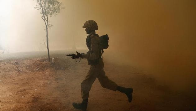 An Indian Army soldier runs amid smoke from canisters during a session to showcase skills at the Army Service Corps training centre in Bangalore.(AP File Photo)