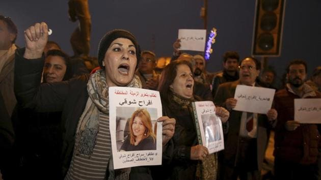 Protesters chant slogans demanding the release of kidnapped journalist Afrah Shawqi al-Qaisi, seen in posters, during a demonstration, in Baghdad. Late Monday night unidentified gunmen broke into the house of al-Qaisi, a journalist and activist in Baghdad and kidnapped her.(AP Photo)