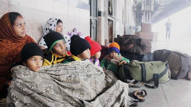 Passengers wrap themselves in woollens as they wait for their trains on a cold and foggy morning at Allahabad Railway Station on Thursday. The fog delayed about 60 trains while 20 were rescheduled in north India.(PTI Photo)