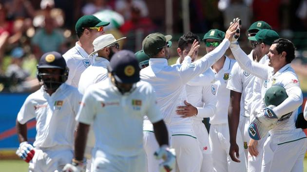 South African players celebrate the dismissal of Sri Lanka batsman Kusal Janith Perera (front) during the fourth day of the first Test.(AFP)