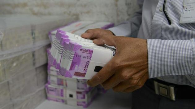 A bank employee checks stacks of new 2000 rupee notes in Ahmedabad on November 11, 2016.(AFP Photo)