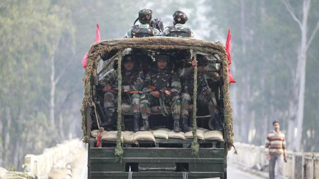 Soldiers patrol a highway outside an army base in Nagrota.(AP Photo)