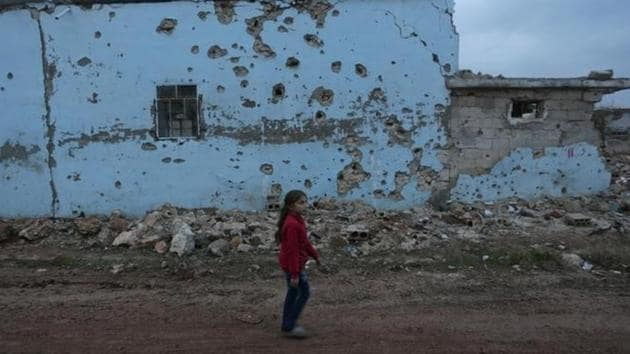 A girl walks past a damaged house in al-Rai town, northern Aleppo province in Syria.(Reuters photo)