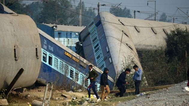 Officials and bystanders gather at the derailed train carriages at Rura, some 30 kms west of Kanpur on December 28, 2016, following a train crash in the northern Indian state of Uttar Pradesh.(AFP Photo)